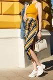 一名妇女黄色上面的和裙子的穿过城市, h走 免版税图库摄影