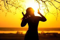 一名妇女,享受在日落的女孩的剪影耳机的音乐 免版税库存图片