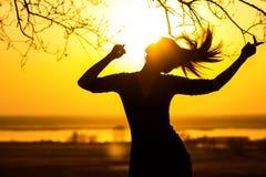 一名妇女,享受在日落的女孩的剪影耳机的音乐 库存照片