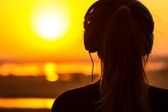 一名妇女,享受在日落的女孩的剪影耳机的音乐 免版税库存照片