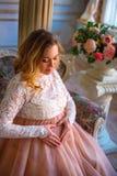 一名孕妇在一件美丽的礼服坐长沙发 母性的概念 库存图片