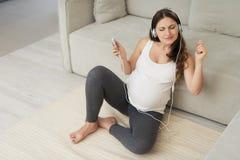 一名孕妇在家坐一个轻的地板 她佩带了耳机并且听到音乐 免版税库存照片