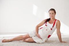 一名孕妇坐地板谈话与腹部的一个婴孩 免版税库存图片