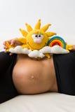 一名孕妇有在她的胃的一个玩具 库存照片