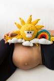 一名孕妇有在她的胃的一个玩具 免版税库存图片