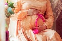 一名孕妇的腹部一件桃红色礼服的有在腰部的一把弓的 免版税库存图片