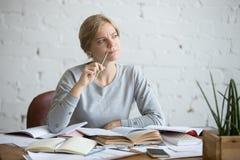 一名学生妇女的画象书桌的,皱眉 免版税库存图片