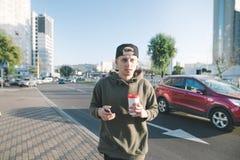 一名学生的画象有一杯咖啡的和一个电话在他的手上,当走在城市、路和汽车附近时 生活方式a 免版税库存照片