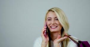 一名对一个电话的年轻快乐的妇女答复的特写镜头英尺长度在手机和有关于她的购物的一次谈话 股票录像
