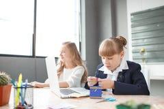 一名小女实业家工作在计算机和由雇员帮助 库存图片