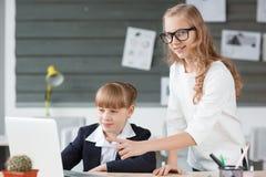一名小女实业家工作在计算机和由雇员帮助 免版税库存图片