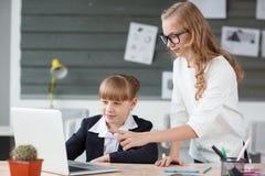 一名小女实业家工作在计算机和由雇员帮助 免版税库存照片