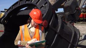 一名少妇工作者在猎物挖掘机的一个大杓子附近站立 影视素材