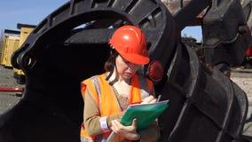 一名少妇工作者在猎物挖掘机的一个大杓子附近站立 股票录像