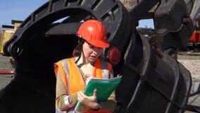 一名少妇工作者在猎物挖掘机的一个大杓子附近站立 股票视频