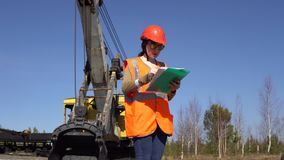 一名少妇工作者在采矿挖掘机附近站立,看在项目 股票视频