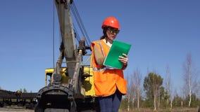 一名少妇工作者在采矿挖掘机附近站立,看在项目 股票录像