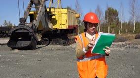 一名少妇工作者在采矿挖掘机附近站立,看在项目 影视素材