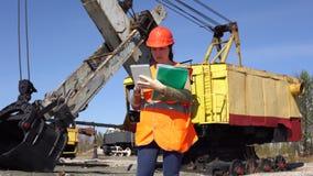一名少妇工作者在采矿挖掘机附近站立 股票视频