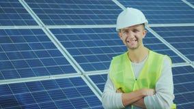 一名工作者的画象总体的和在太阳电池板背景的一件盔甲  微笑,神色到照相机里 免版税库存图片
