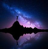 一名常设妇女的银河和剪影山的 免版税库存照片