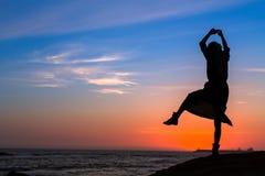一名年轻乐趣妇女的剪影海海滩的在惊人的日落 业余爱好 库存图片