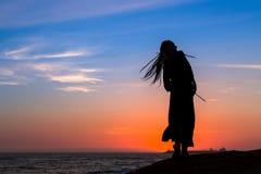 一名年轻乐趣妇女的剪影海海滩的 库存照片