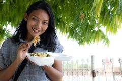 一名年轻亚裔妇女吃典型的缅甸食物 免版税库存图片