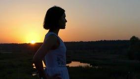 一名年轻亭亭玉立的妇女在湖银行站立在精采日落在Slo Mo 股票视频