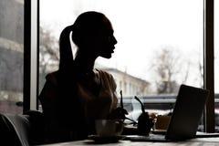 一名年轻亭亭玉立的妇女的剪影有坐在桌上的长的头发的 图库摄影
