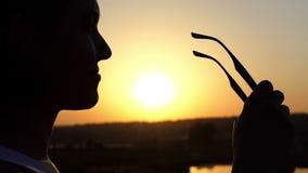 一名年轻亭亭玉立的妇女站立并且离开她的太阳镜在日落在Slo Mo 股票视频