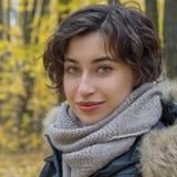 一名年轻俏丽的妇女的画象在一个金黄秋天公园 免版税库存图片