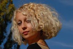 一名年轻俏丽的妇女的画象有一双白肤金发的卷发和蓝眼睛的在蓝天下 免版税库存照片