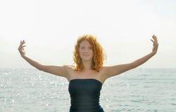 一名年轻典雅的红发卷曲妇女的愉快的愉快的画象有被伸出的胳膊的由海滩的海在有拷贝的意大利 库存照片