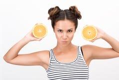 一名年轻动态妇女的画象有两个橙色切片的 图库摄影