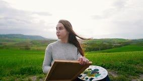 一名年轻可爱的妇女在绿色领域和凹道中间坐 在风吹的头发 股票视频