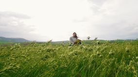 一名年轻可爱的妇女在麦田和凹道中间坐 影视素材