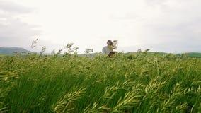 一名年轻可爱的妇女坐山坡和凹道 并且风吹 影视素材