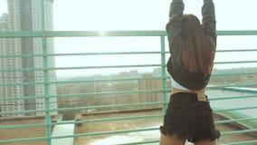 一名年轻可爱的妇女是跳舞和舒展与都市风景反对朝阳的背景 ??  股票录像