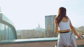 一名年轻可爱的妇女是跳舞和舒展与都市风景反对朝阳的背景 ??  影视素材