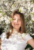 一名年轻可爱的妇女的垂直的画象在开花的庭院里 与她的闭上的眼睛的微笑 库存图片