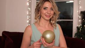 一名年轻可爱的白肤金发的妇女的画象在她的手上的拿着圣诞节玩具 股票录像