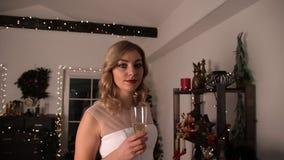 一名年轻可爱的白肤金发的妇女的画象有一杯的香槟 影视素材
