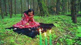 一名年轻吉普赛妇女在森林投掷小卵石并且做不可思议的运动用她的在灼烧的蜡烛的手 股票录像