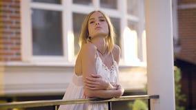 一名年轻和浪漫妇女的画象有被折叠的头发的,在一个开放阳台站立在一夏天和温暖的天 股票录像