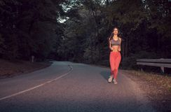 一名年轻妇女,跑步的跑在柏油路,户外 库存图片