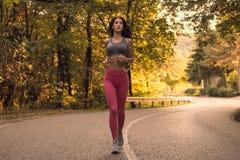 一名年轻妇女,跑的跑步,森林森林,沥青ro 图库摄影