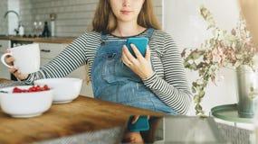 一名年轻孕妇在厨房里坐在桌上,有早餐,饮用的茶和使用智能手机 库存照片