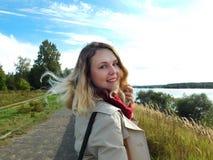 一名年轻微笑的妇女的画象 女孩有在码头的步行并且转过来 库存图片