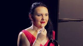 一名年轻深色的妇女申请在她的嘴唇的光泽有刷子的 影视素材